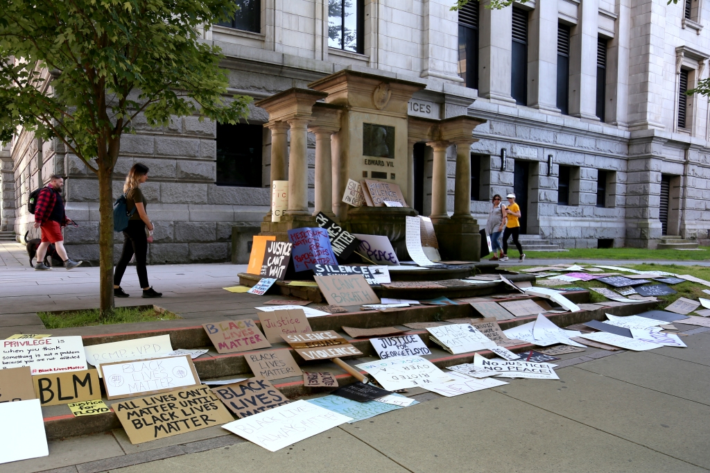 a long shot of signs laid-off on the side walk of Vancouver Art Gallery.