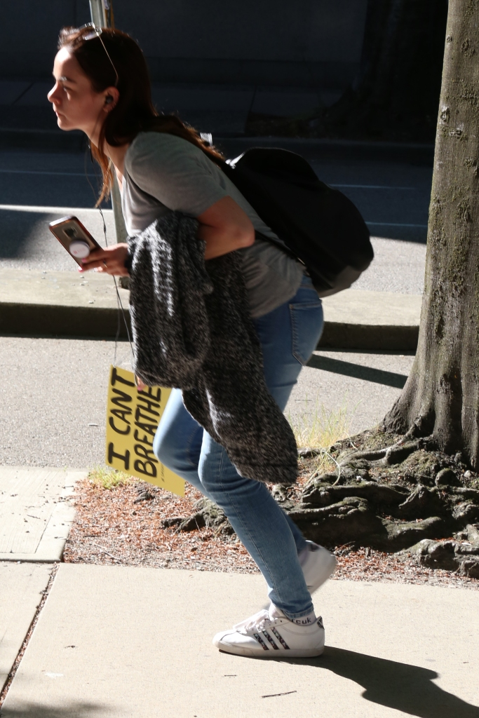 "A person in gray grabbing a sign on a sidewalk wrote, ""I cant breathe""."