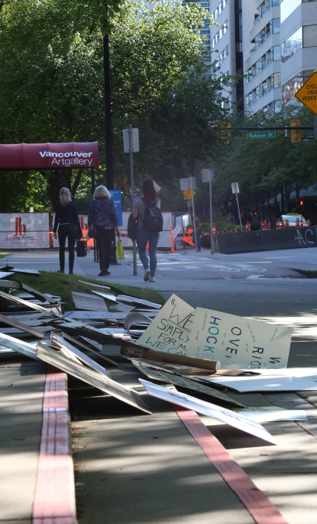 A vertical long shot of a sidewalk with signs on the ground.